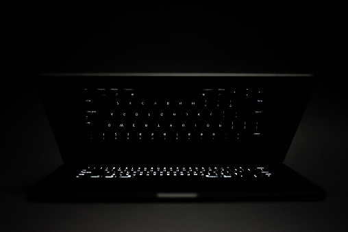 Apple MacBook Pro laptop with glowing keyboard isolated