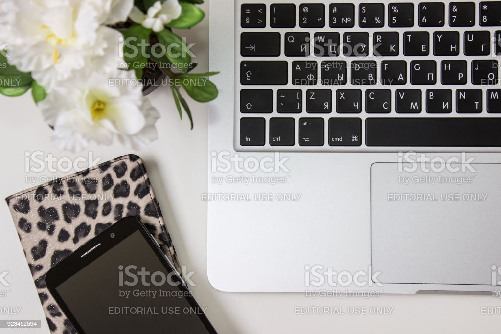 Apple Macbook Pro Retina on a desk, table with beautiful stationery and smart phone. Mockup for decal, sticker design. Trendy office, freelance workplace, top view stock photo