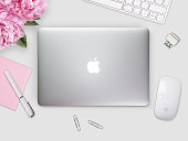 Apple Macbook Retina cover on a desk, table with mouse and stationery.