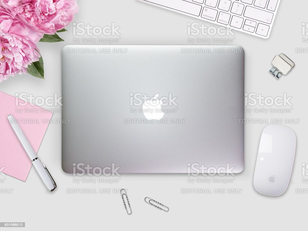 Apple Macbook Retina cover on a desk, table with mouse and stationery. stock photo