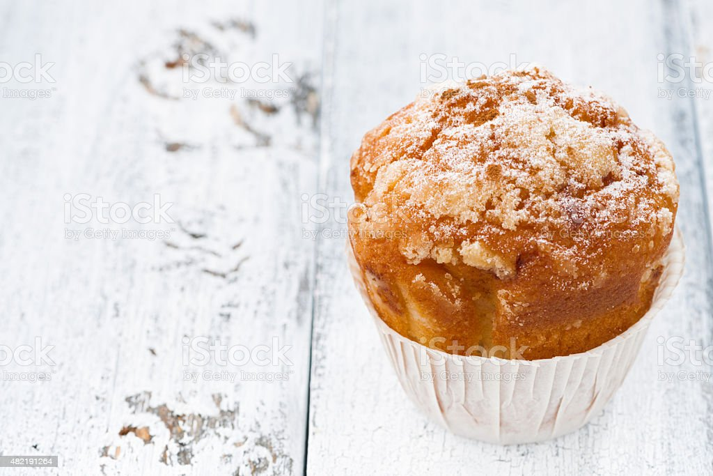 Apple muffin with icing sugar on white wooden background stock photo