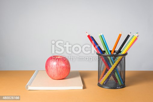 istock apple on a notebook and A stack of color pencils 485526166
