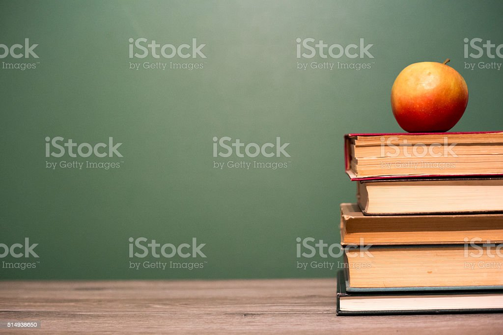 Apple on a pile of books. stock photo
