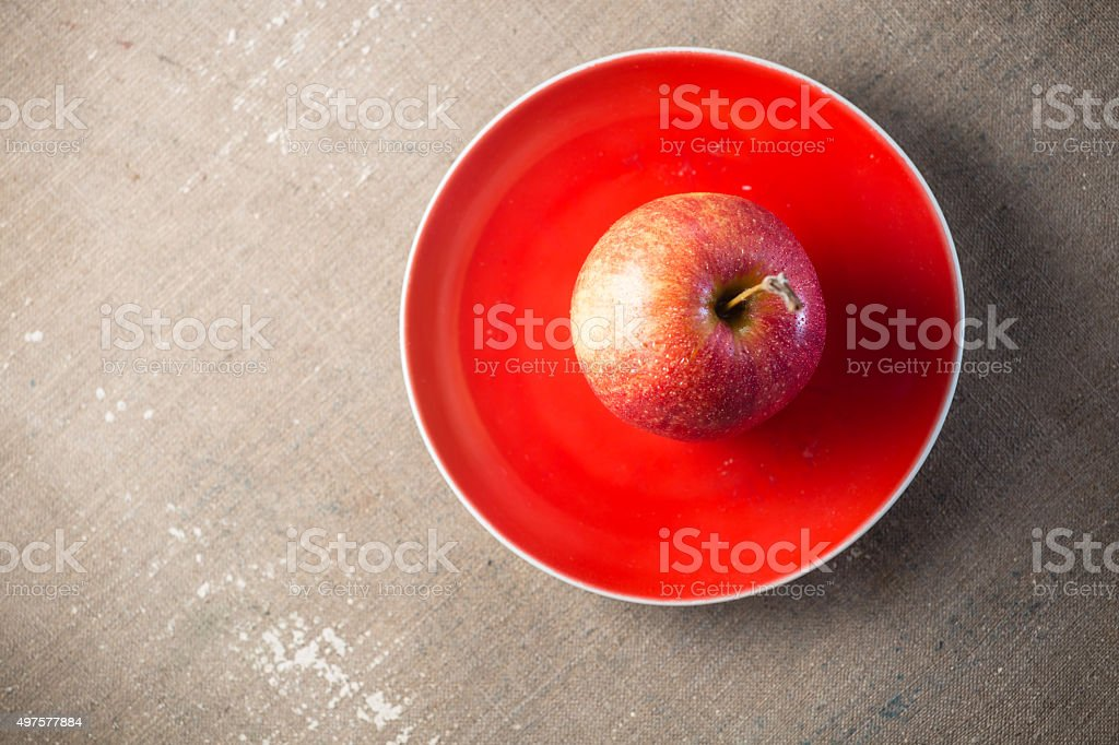 Apple on a red plate stock photo