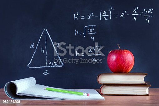 istock Apple on book and green wooden pen on opened notebook on desk 989474206