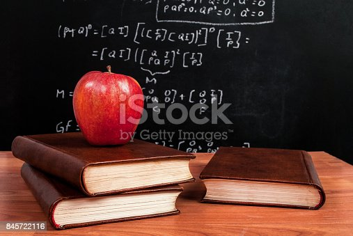 istock Apple on books on a wooden desk during math class in the classroom 845722116