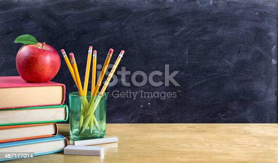 istock apple on books with pencils and empty blackboard 487177014