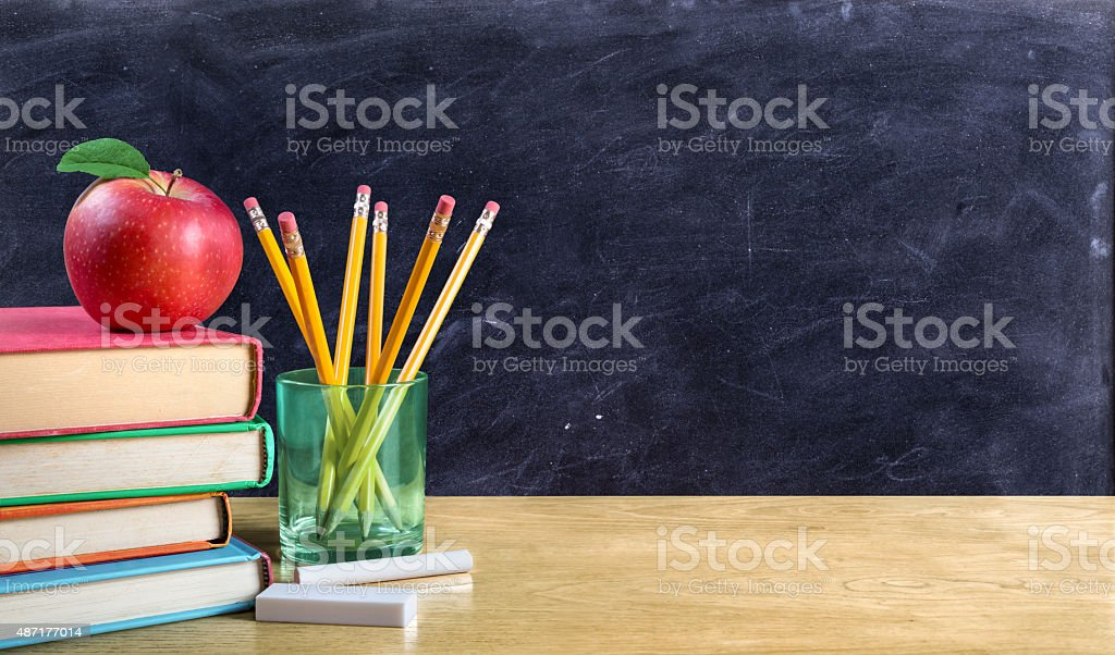 apple on books with pencils and empty blackboard stock photo