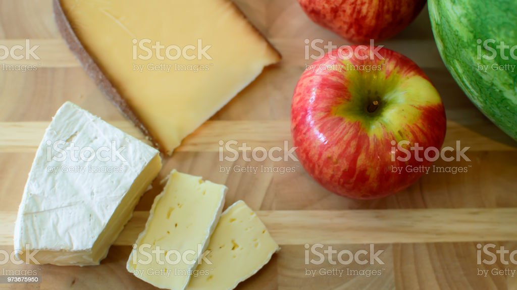Apple on cheese plate with fresh watermelon and roses in kitchen stock photo