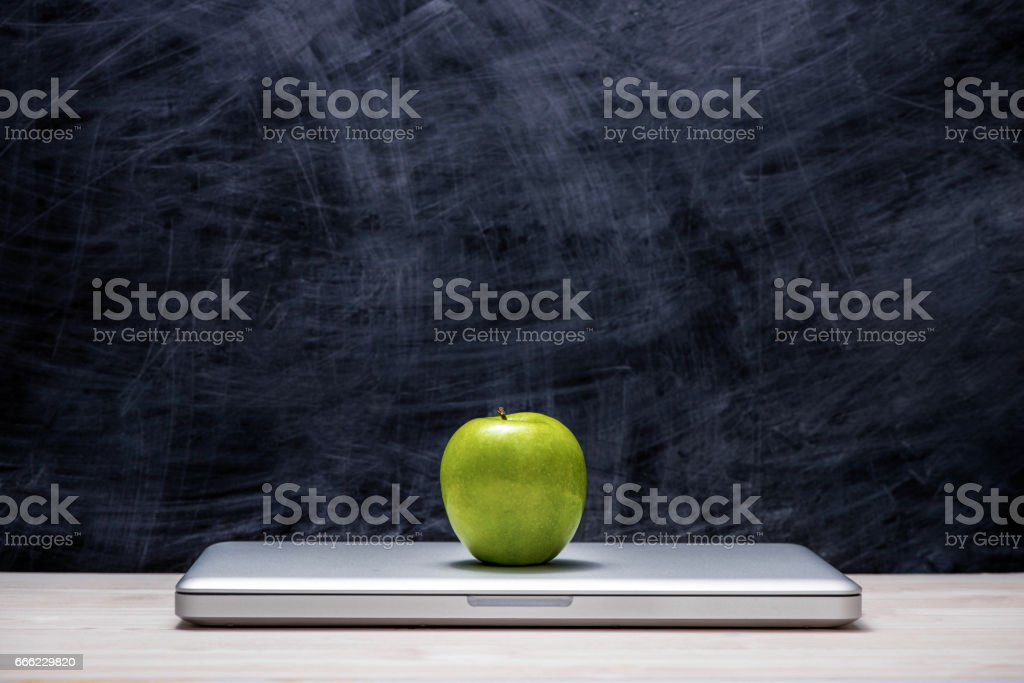 Apple on laptop on table in front of chalkboard. stock photo