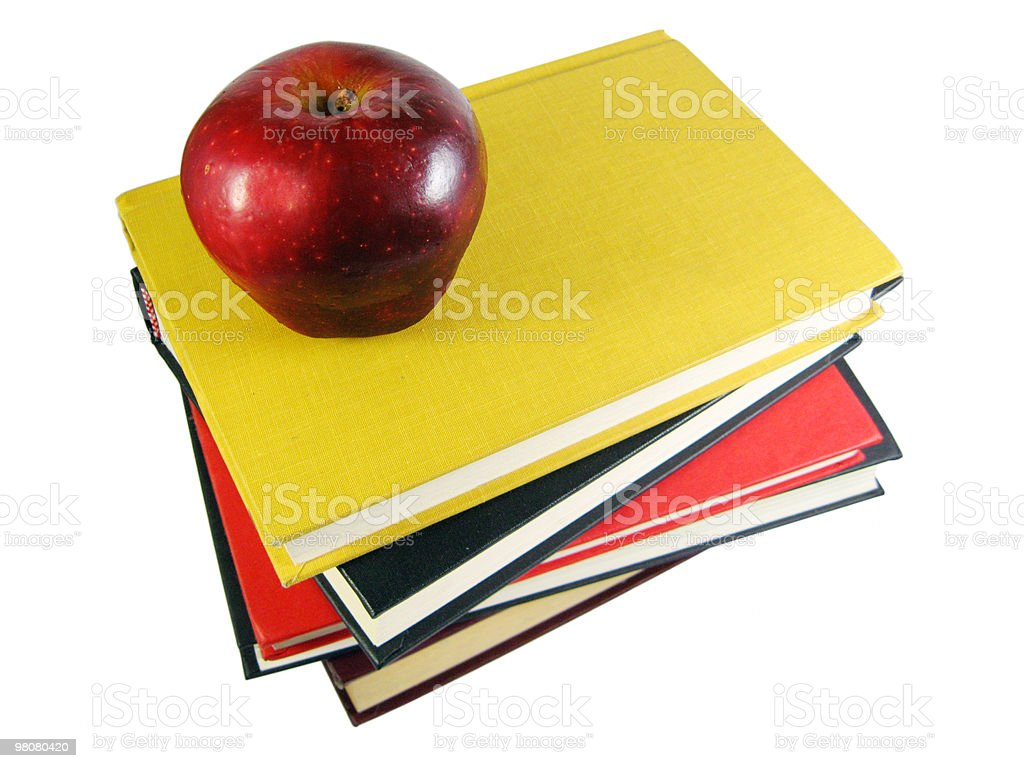 Apple on stack of black, yellow, red books royalty-free stock photo
