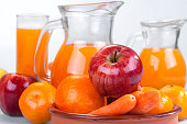 apple, orange and carrots with fresh juice in the background
