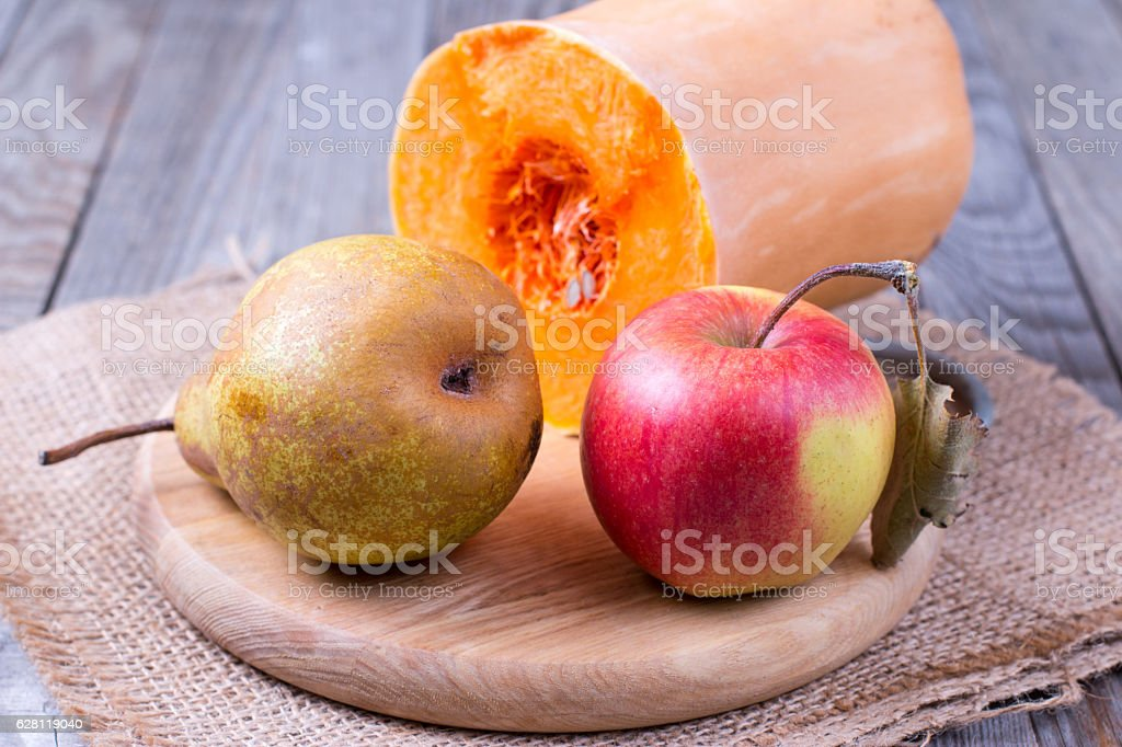 apple, pear and pumpkin on a wooden background stock photo