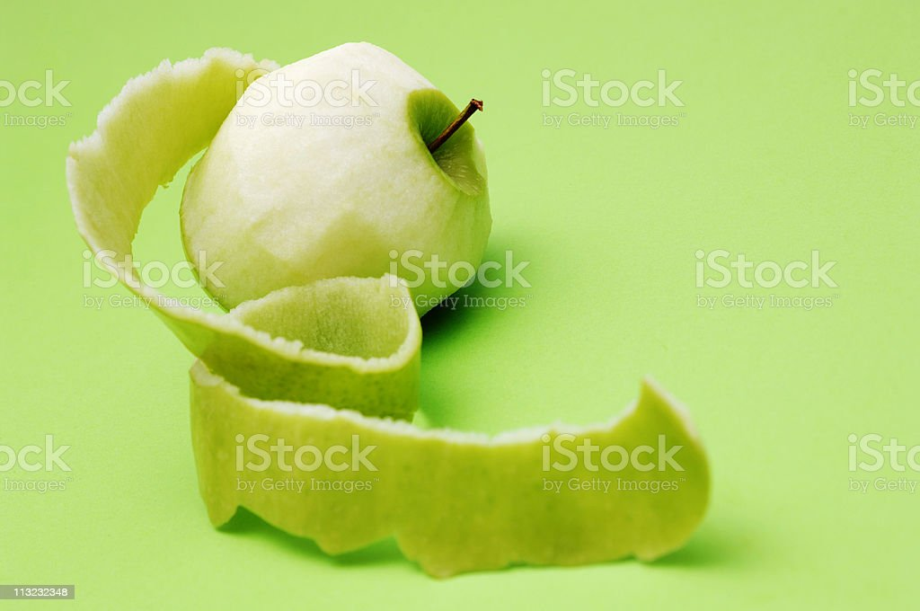 Apple peeled with twisting skin against green royalty-free stock photo