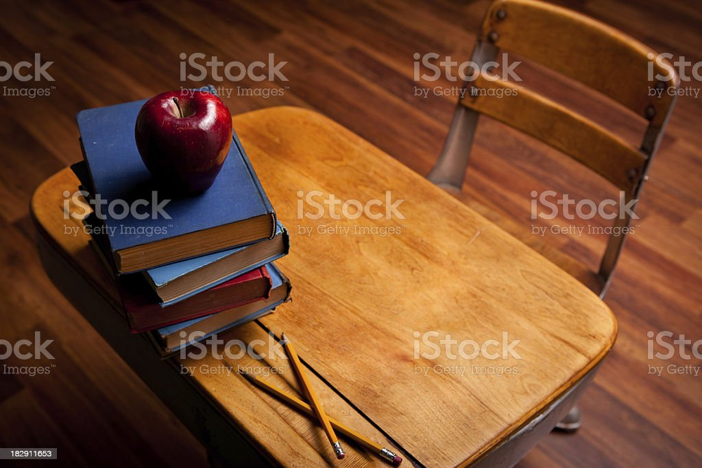 Apple, Pencils, Old Books on School Desk and Hardwood Floor royalty-free stock photo