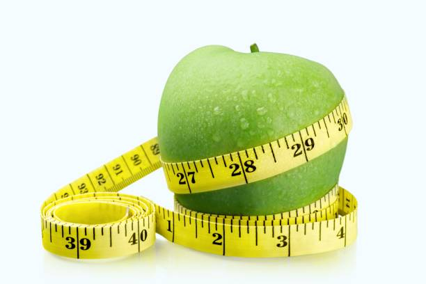 Apple. Green apples measured the meter on light background tape measure stock pictures, royalty-free photos & images
