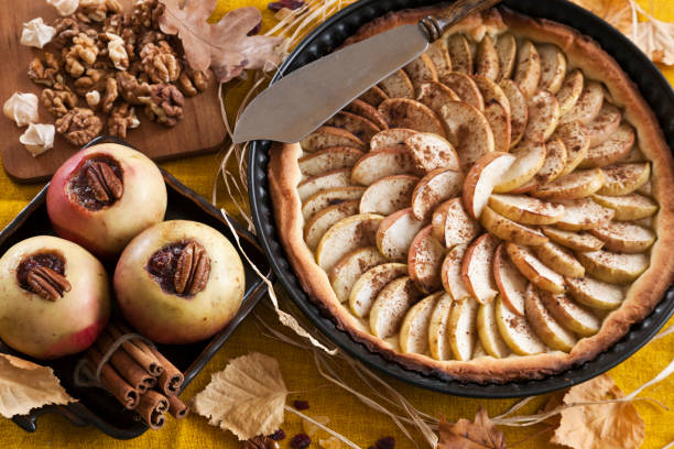 apfelkuchen und äpfel gebacken mit zimt und marmelade von herbstlaub auf einem vintage holz-hintergrund umgeben. - bratäpfel stock-fotos und bilder
