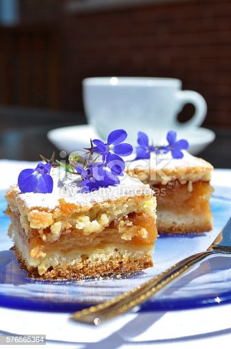 Homemade apple pie on a blue plate,blue tiny flowers as a decoration. White cup in the background. Vertical.