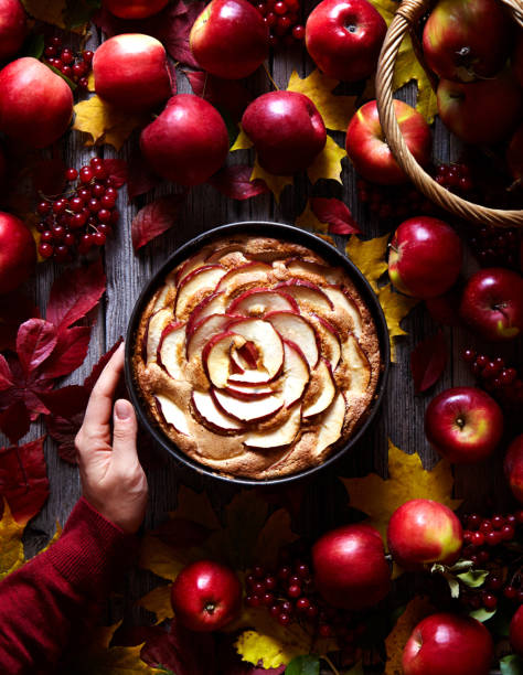 Apple pie cake decorated with slices in the baking dish on a wooden background red apples. stock photo