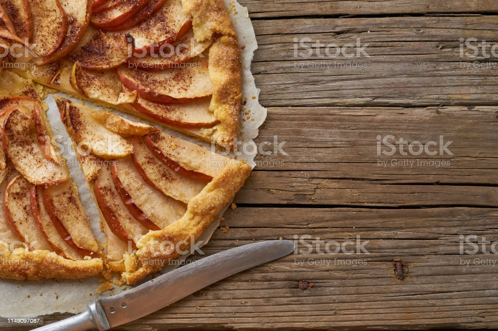 Apple pie, galette with fruits, sweet pastries on old wooden rustic...