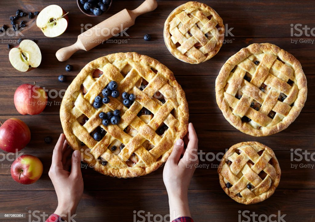 Apple pie on the kitchen wooden table with apples and rolling pin. Hands in the frame. Traditional dessert for Independence Day. Dark food photo stock photo