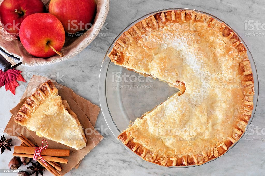 Apple pie, overhead scene with cut slice on marble background stock photo