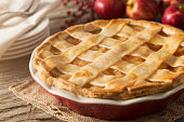 A lattice apple pie.  The apple pie is set in a fall scene with apples, dessert plates, forks, and seasonal decoration.  The pie is set on a rustic farm table with burlap textured hot pad.  This image could be used to illustrate:  Baking, Fall, Autumn, Thanksgiving, Apple pie, holiday desserts, holiday recipes, etc