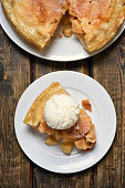 Piece of apple pie served with ice cream, fruit baking on wooden background, top view