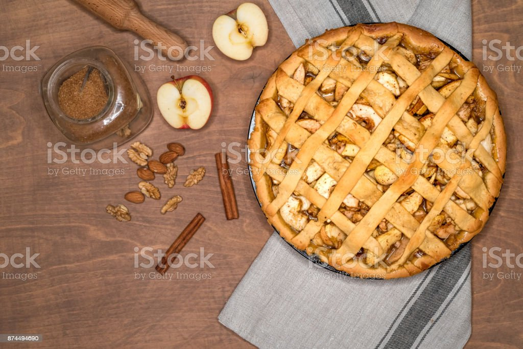 Apple pie tart with raisins, nuts and cinnamon on vintage wooden background texture. Traditional dessert for Independence Day in America. Rustic style. Top view stock photo