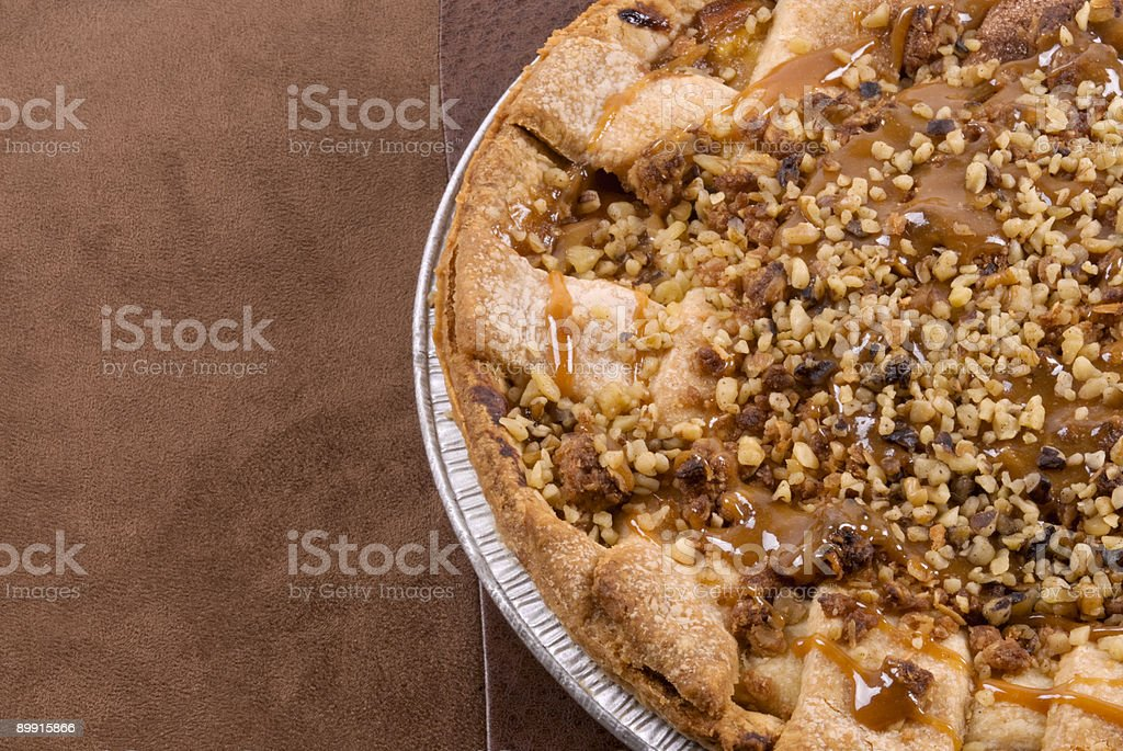 apple pie topped with caramel and walnuts brown leather background royalty-free stock photo