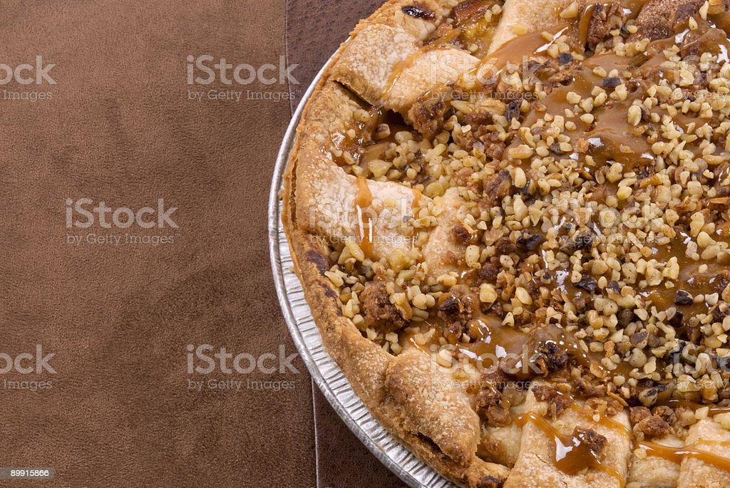 Tarte aux pommes accompagné de caramel et noix fond en cuir marron photo libre de droits