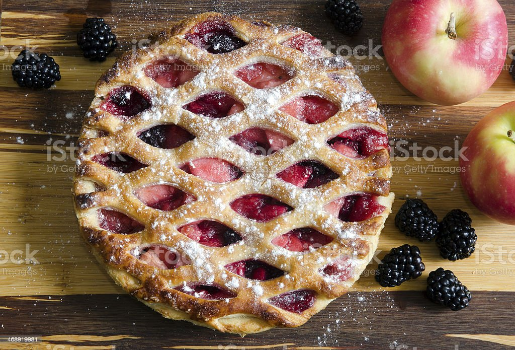Apple pie with berries on wood table stock photo