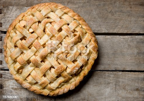 Overhead view of a homemade apple pie. Apples slices peek out of the golden brown lattice crust on this delicious looking homemade apple pie. A brown weathered apple crate is the rustic background used to feature this homespun dessert.