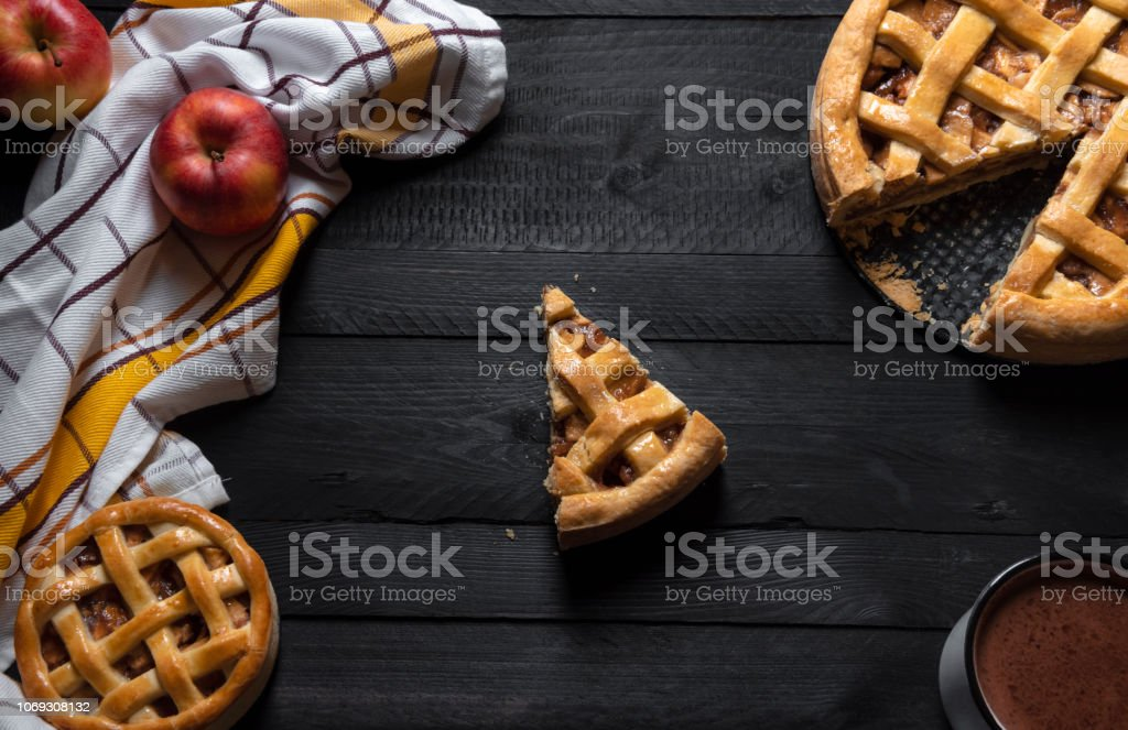 Rustic table with differently sized apple pies and one slice in the...