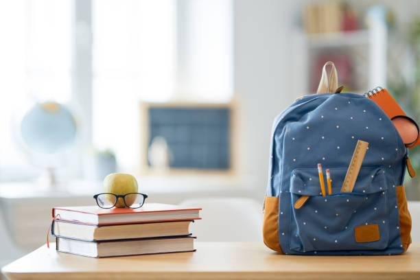 Apple, pile of books and backpack stock photo