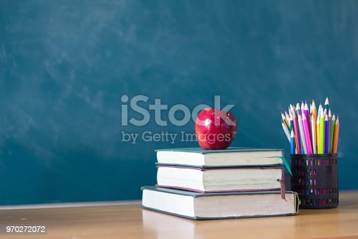 istock Apple puts on a book studying ,The background is blackboard, educational concepts 970272072