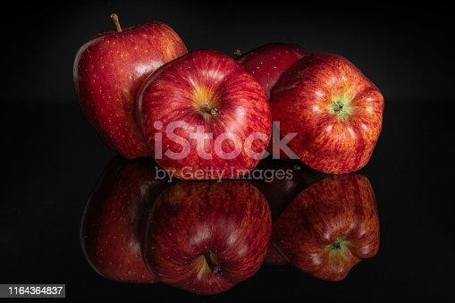 istock Apple red delicious isolated on black glass 1164364837