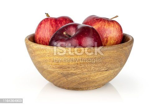 Group of three whole fresh apple red delicious in a big wooden bowl isolated on white background