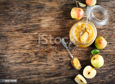 Apple sauce in jars on wooden rustic background, top view, copy space