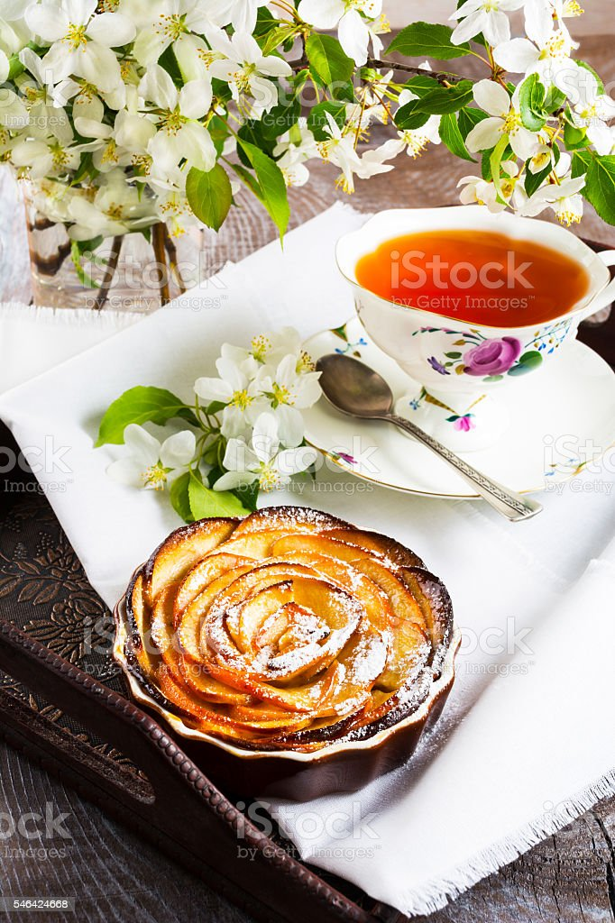 Apple shaped roses pie and cup of tea on tray stock photo
