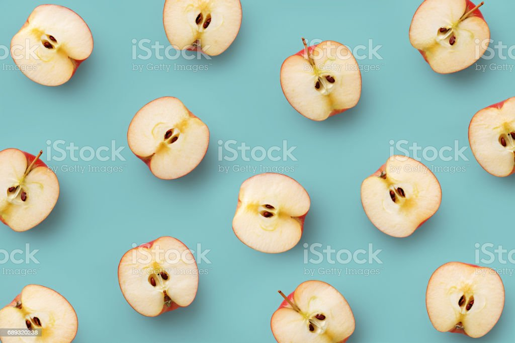 Apple slices pattern on a blue background. Repetition concept. Top view. Flat lay stock photo