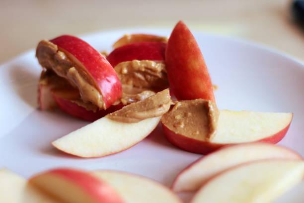 apple segmenten met pindakaas - pindakaas stockfoto's en -beelden