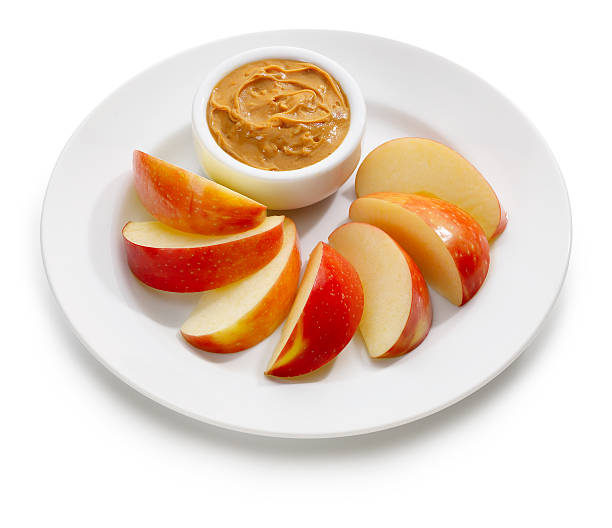 apple slices with peanut butter - pindakaas stockfoto's en -beelden