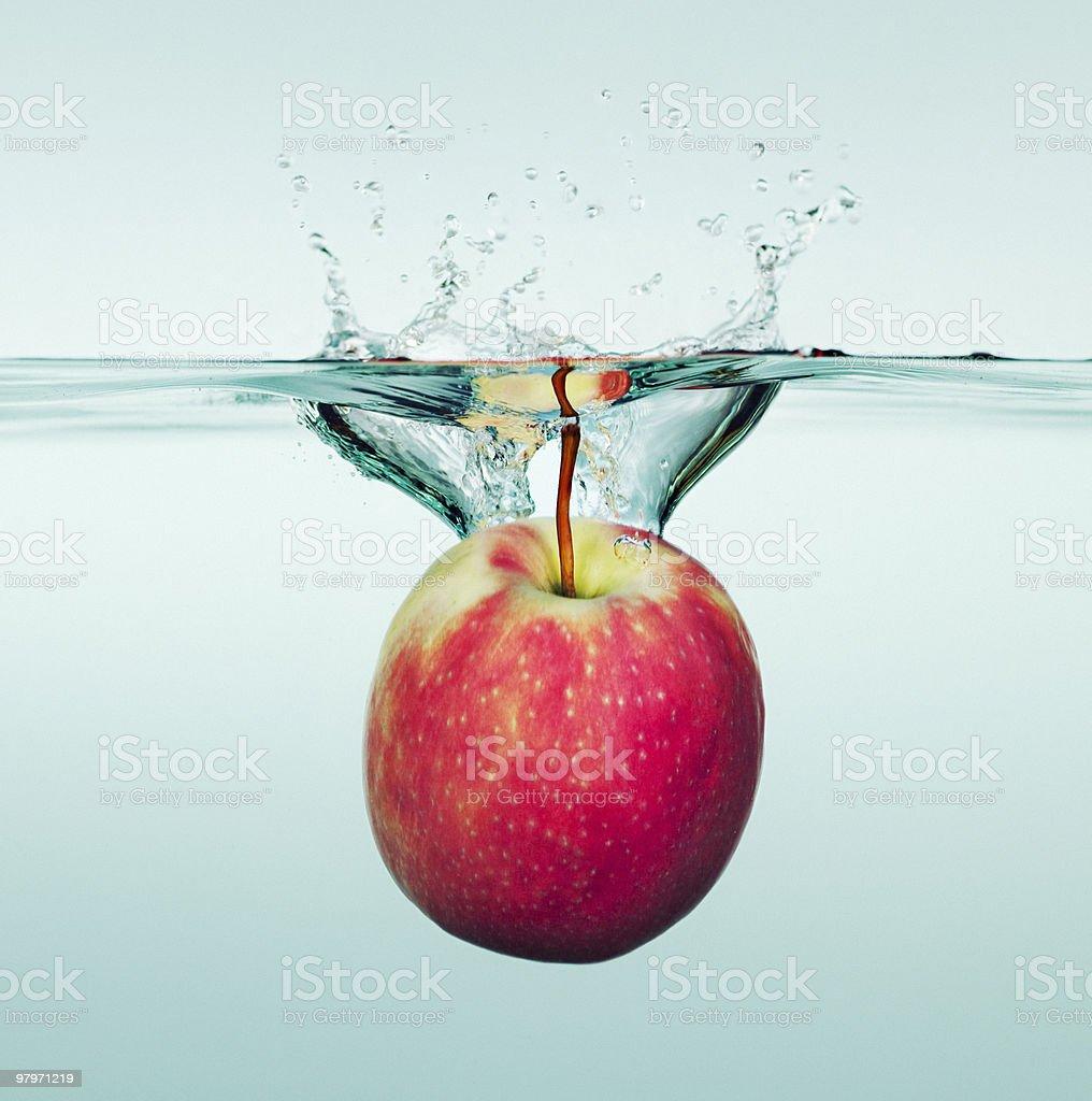 Apple splashing in water royalty-free stock photo