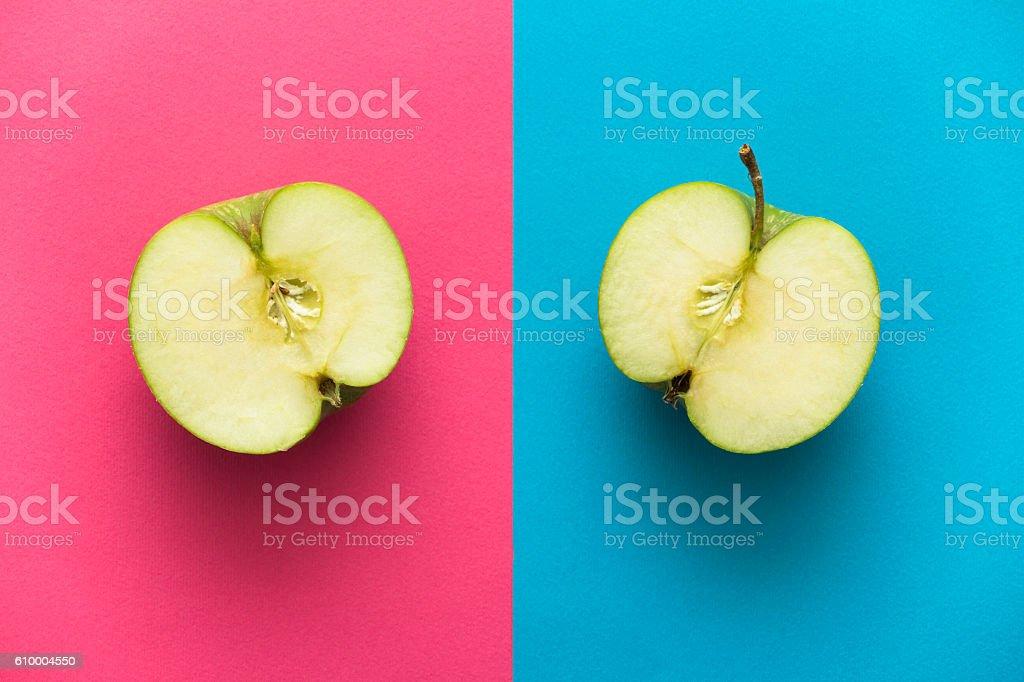 Apple splitted in half on rose quartz serenity blue background stock photo