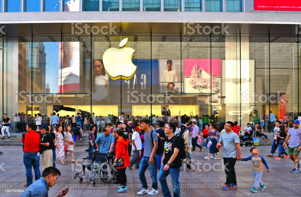 Apple store window with sign in Nanjing East Road with people who often line up to grab on one of the company's latest gadgets. Shanghai China 13.05.2017. Apple store window with sign in Nanjing East Road with people who often line up to grab on one of the company's latest gadgets. Shanghai China Apple Computers Stock Photo
