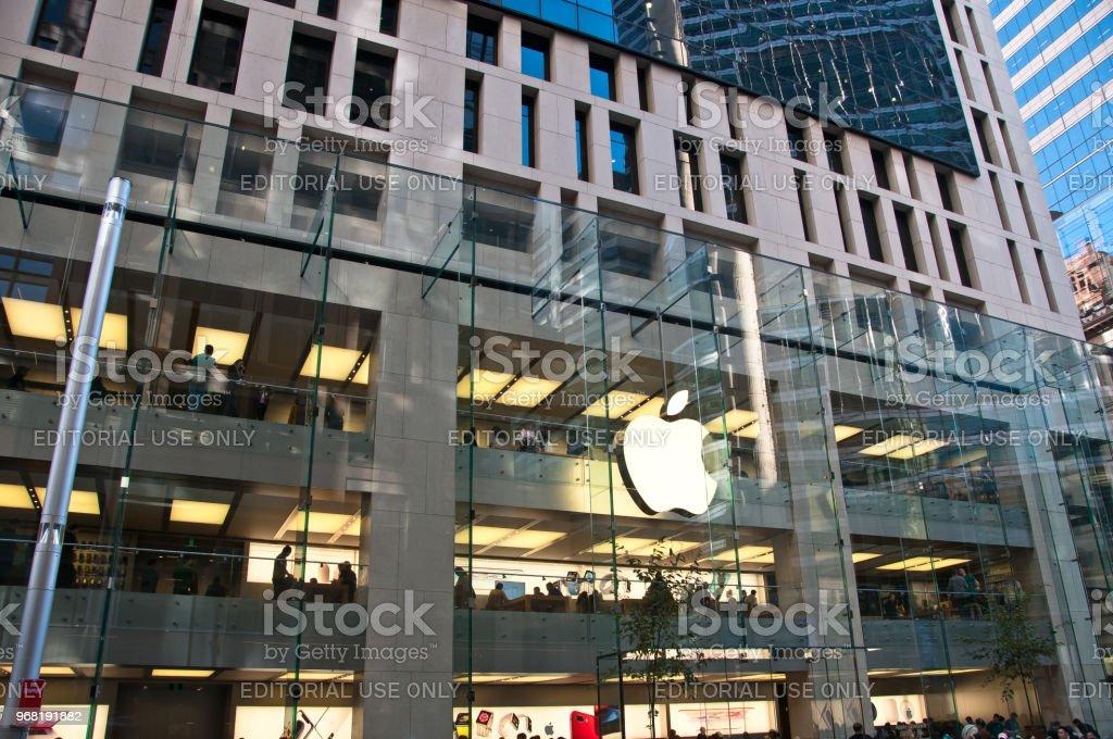 Loja de Apple com um logotipo de apple branco grande em uma parede de vidro no centro da cidade de Sydney. Apple é uma empresa de tecnologia multi Corporação Nacional dos EUA. - foto de acervo