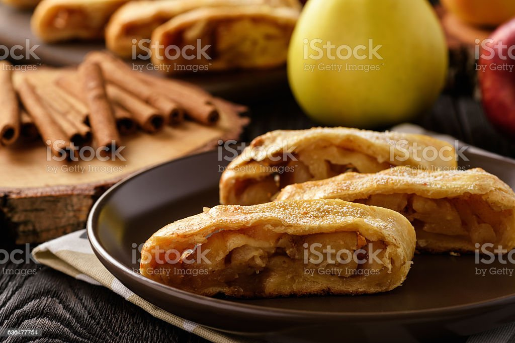 Apple strudel with cinnamon on wooden background. stock photo