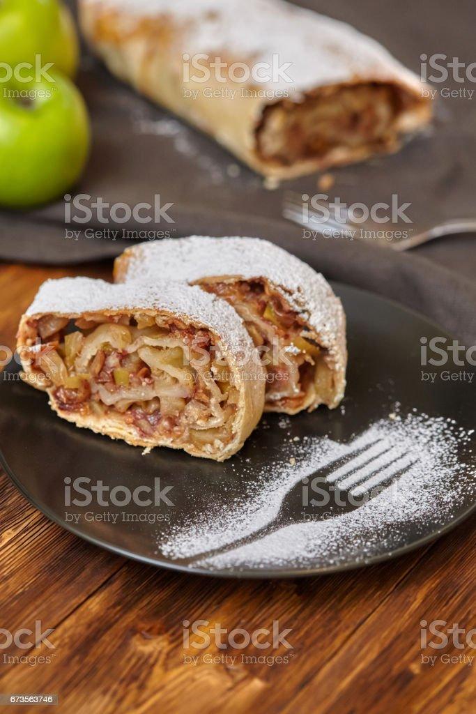 Apfelstrudel mit Puderzucker auf schwarzem Teller, hölzernen Hintergrund – Foto