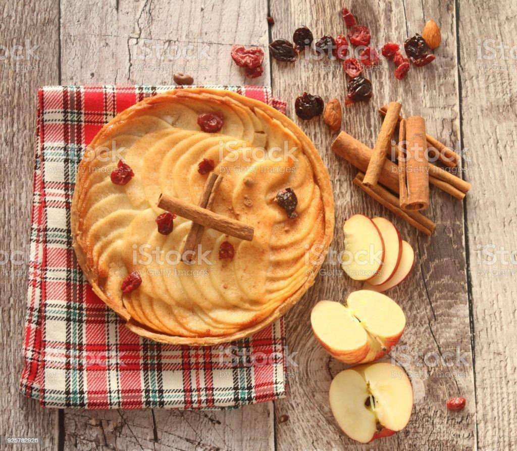 apple tart, apples and cinnamon sticks on wood background stock photo